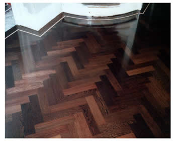 New parquet wood flooring, Guildford. Wenge parquet wooden floor in a herringbone pattern with a maple border..