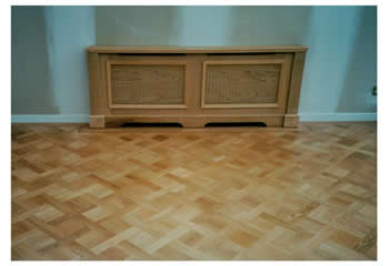 New parquet wood flooring installation in Cambridge. We installed this oak parquet wood flooring in a basket weave pattern with a large dot inset design and mahogany two-line border..